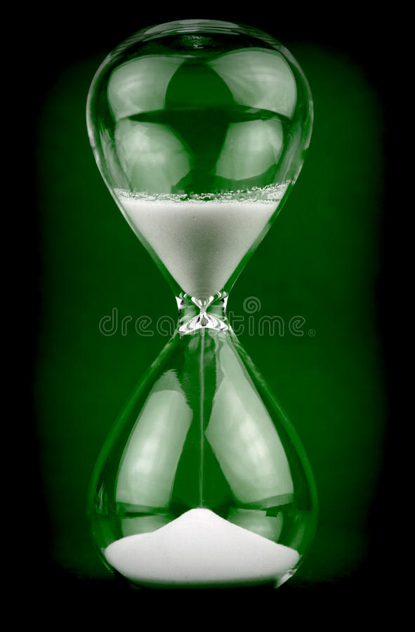 Hourglass on black and green background