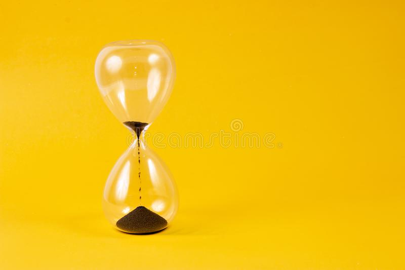 hourglass on yellow background stock photography