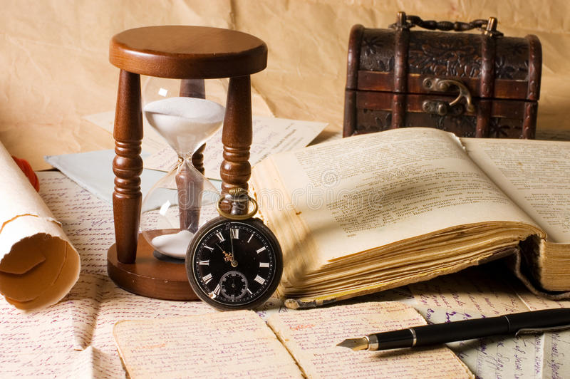 Hourglass and the book - vintage stock photo
