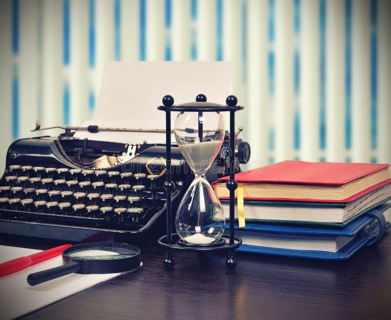 Hourglass, books and typewriter. Hourglass, books and vintage typewriter on table. Vintage effect stock photo