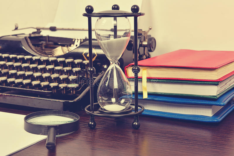 Hourglass, books and vintage typewriter stock photos