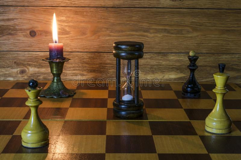 An hourglass, a burning candle and chess pieces  standing on a chess board royalty free stock photo