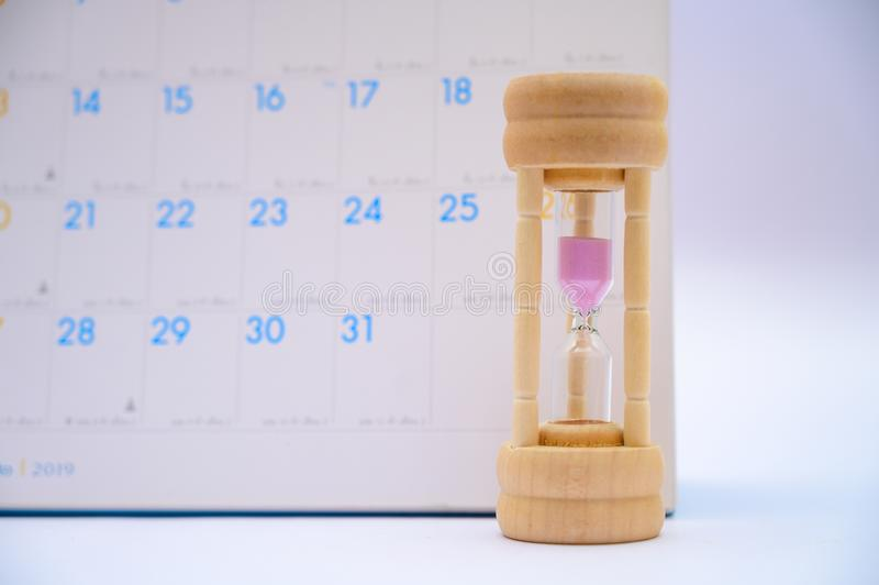 Hourglass with calendar ideas days elapsed time in each period and appointments or waiting royalty free stock photo