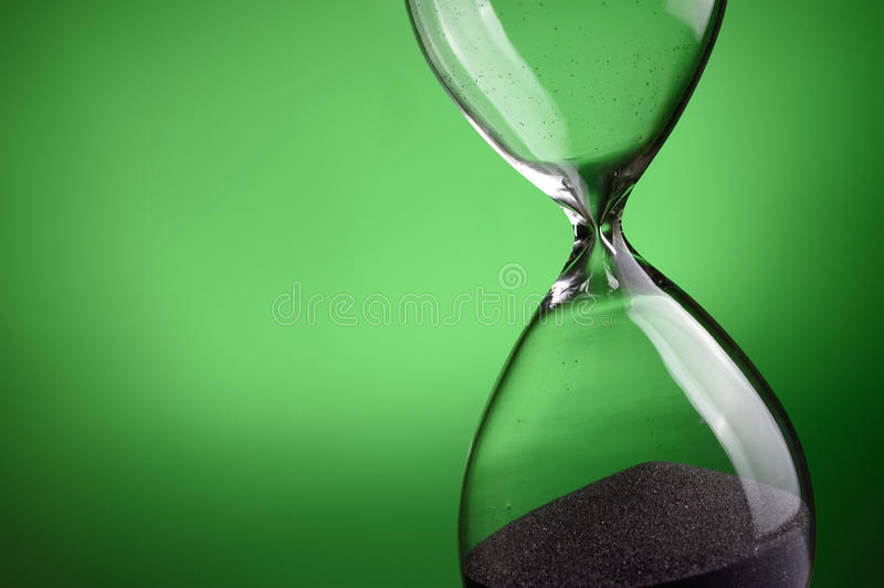 Hourglass. Close-up hourglass on green background stock image
