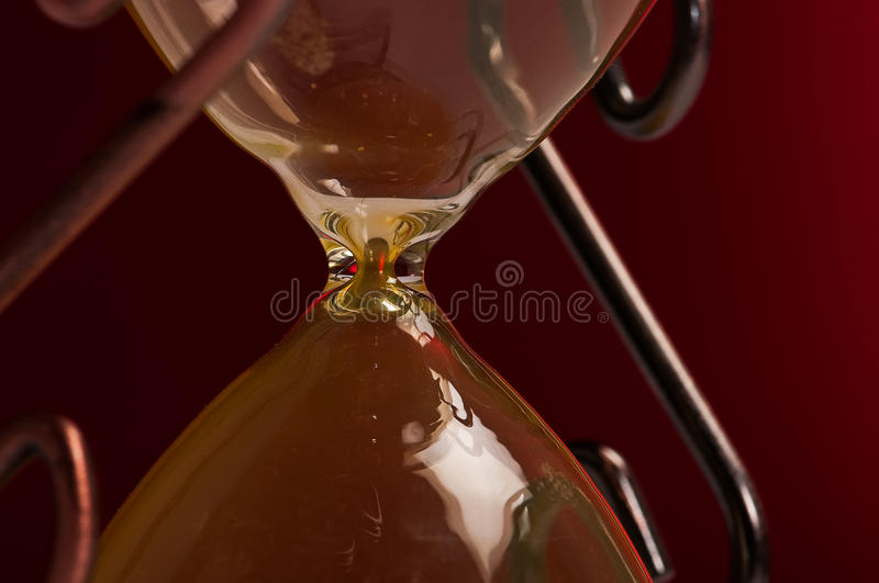 Hourglass closeup. Closeup of the center of an hourglass at its narrowest point where the two halves are joined royalty free stock photos