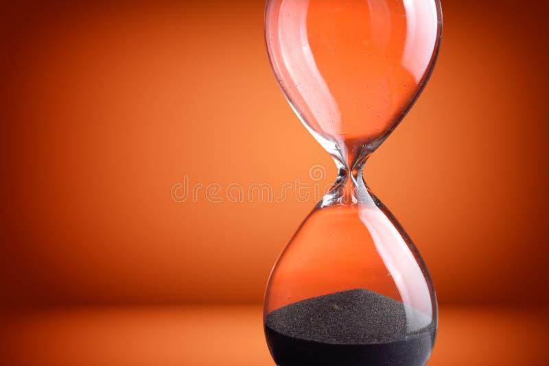 Hourglass. Closeup hourglass on orange background stock photos