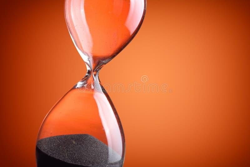 Hourglass. Closeup hourglass on orange background stock photography