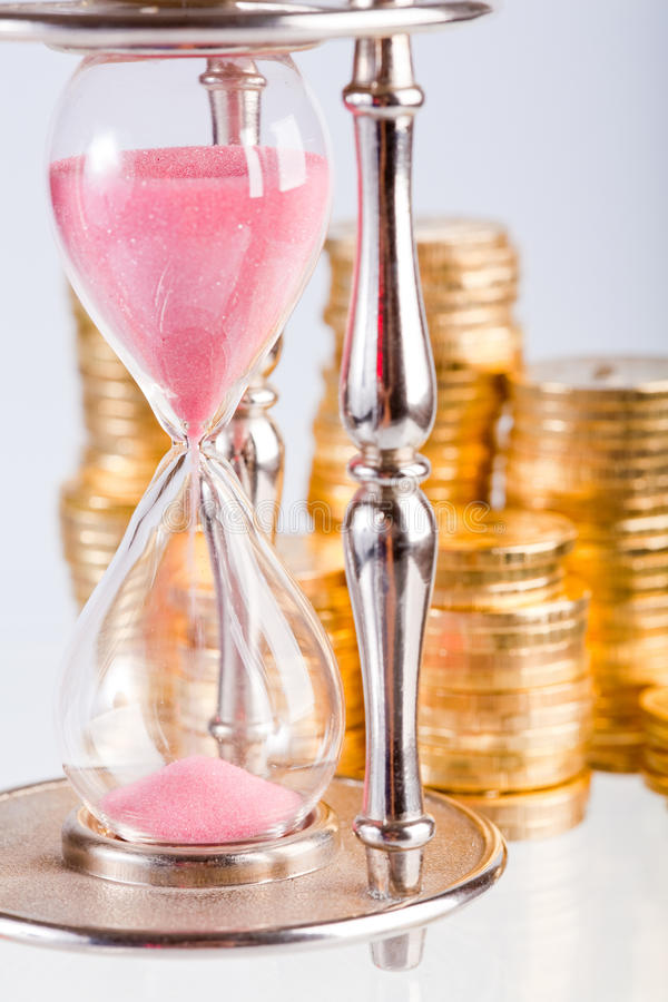 Hourglass and coins. Time is money concept - hourglass and coins stock images