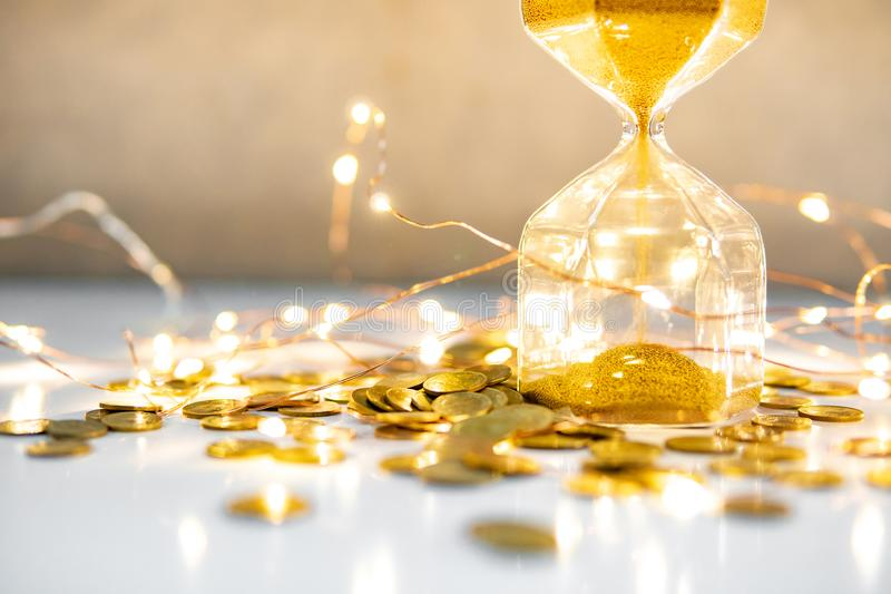 Hourglass and coins on table with decorative lights. Gold sand running through the shape of hourglass with coins and decorative light on the table. Finance stock image