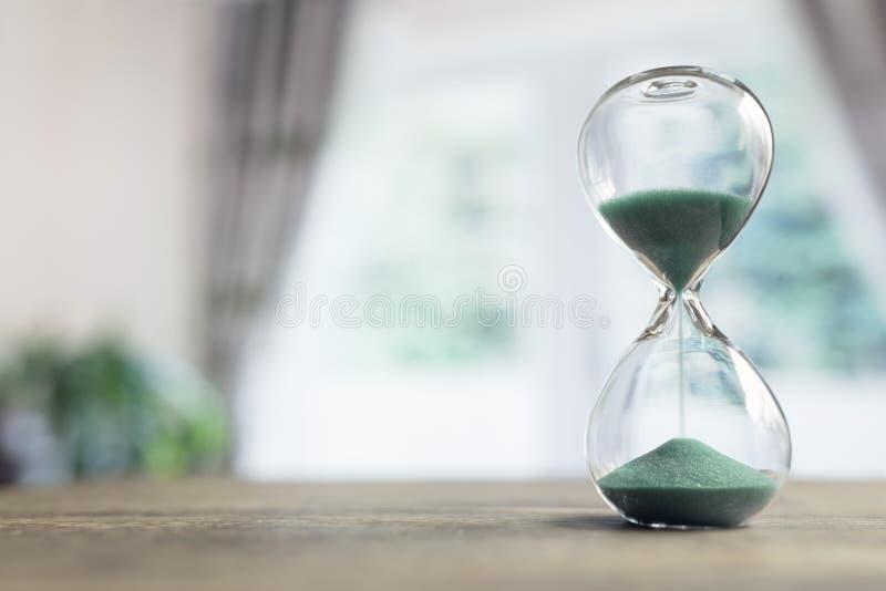 Hourglass czasu omijanie w pokoju okno zdjęcie stock