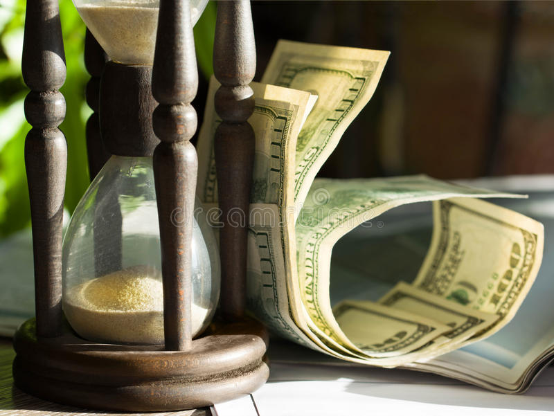 Hourglass and dollar bills. Time is money business philosophy stock images