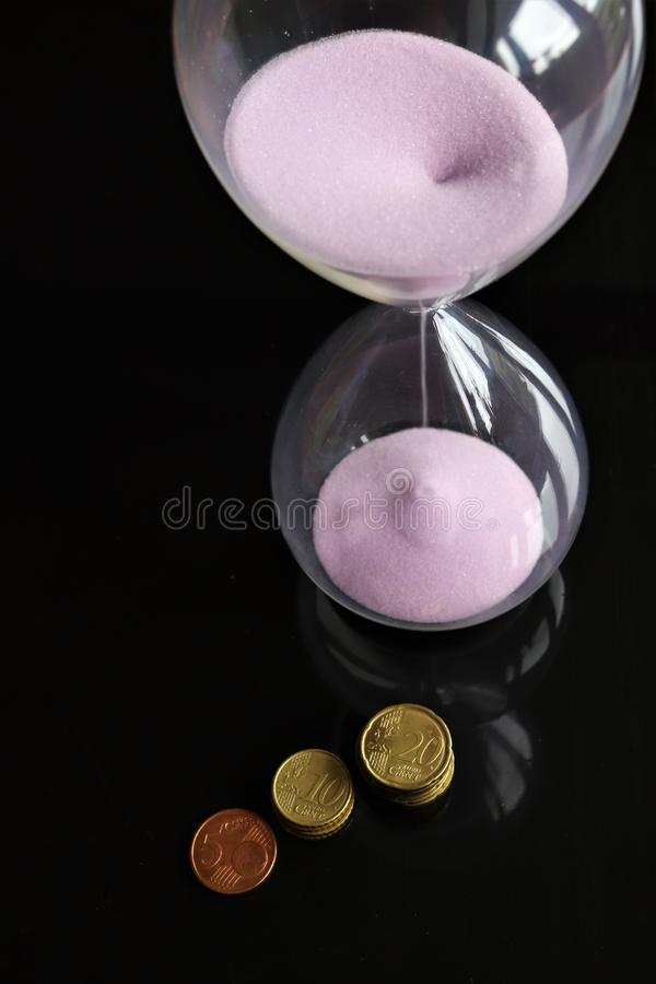 Hourglass and euro cents. Hourglass with pink sand and euro cents isolated on black background royalty free stock photography