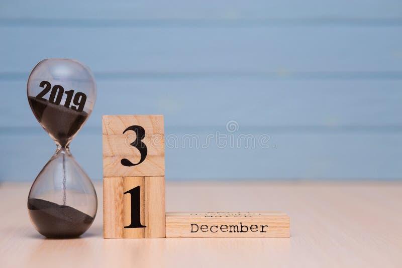 Hourglass falling sand from 2019. December 31st set on wooden calendar. stock photos