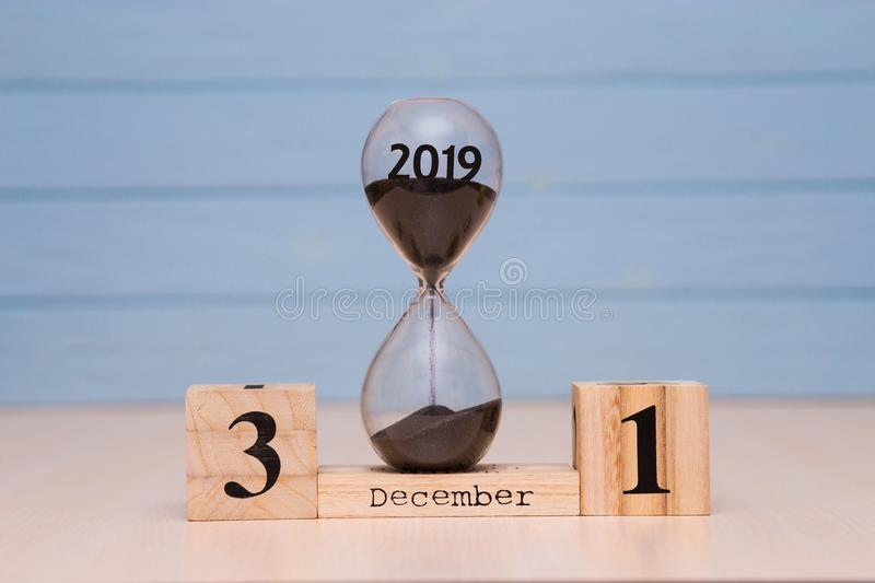 Hourglass falling sand from 2019. December 31st set on wooden calendar. stock photography