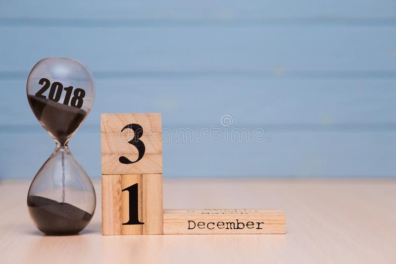 Hourglass falling sand from 2018. December 31st set on wooden calendar. New Year 2019 concept royalty free stock image