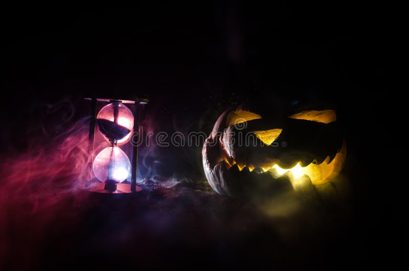 Hourglass. Halloween pumpkin head jack lantern with scary evil faces spooky holiday with burning candles over wooden background. H. Alloween holidays art design stock images