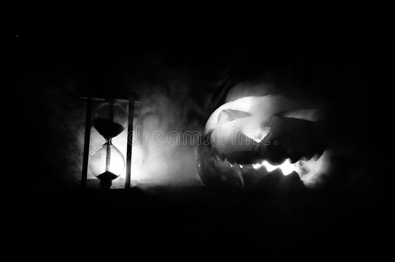 Hourglass. Halloween pumpkin head jack lantern with scary evil faces spooky holiday with burning candles over wooden background. H. Alloween holidays art design royalty free stock photo