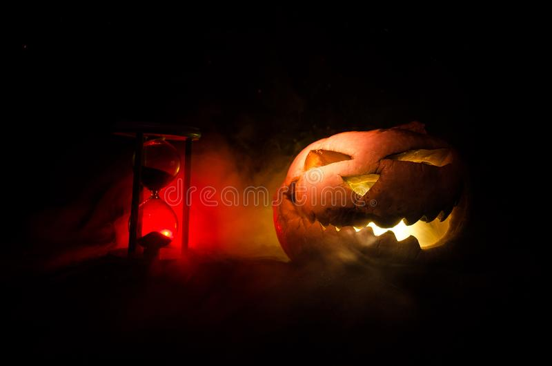 Hourglass. Halloween pumpkin head jack lantern with scary evil faces spooky holiday with burning candles over wooden background. H. Alloween holidays art design royalty free stock photos