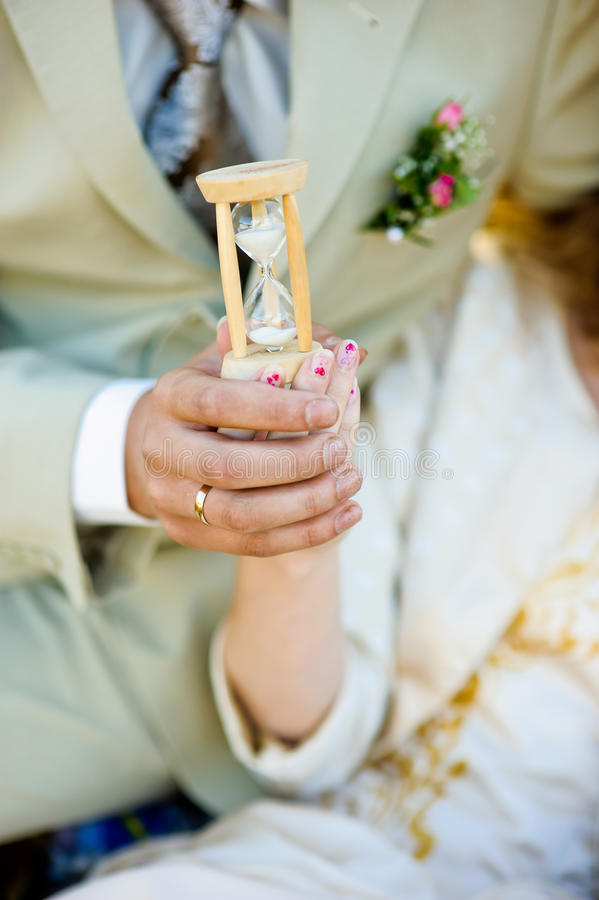 Hourglass in the hands of man and woman.  stock photography
