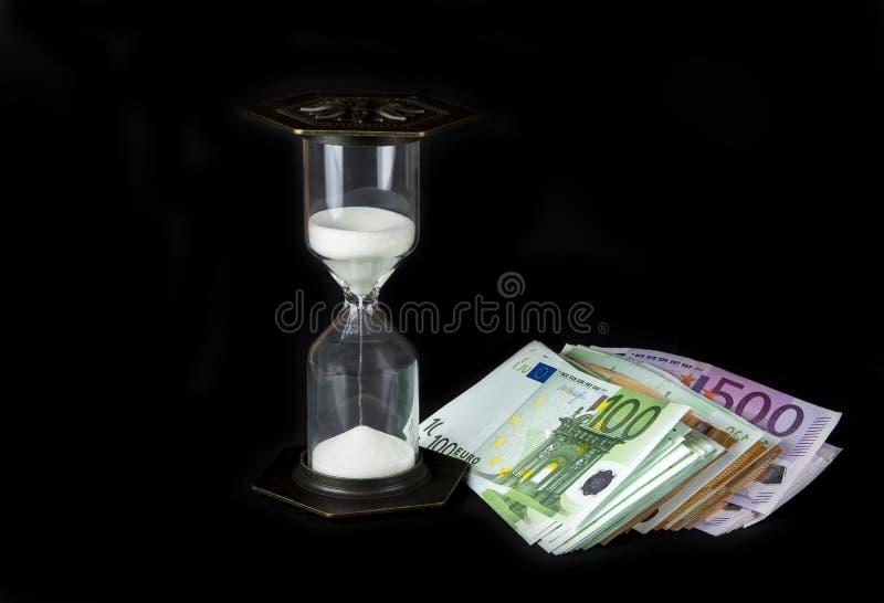 Hourglass i papierowy pieniądze Czas pieniądze pojęciem jest obraz stock