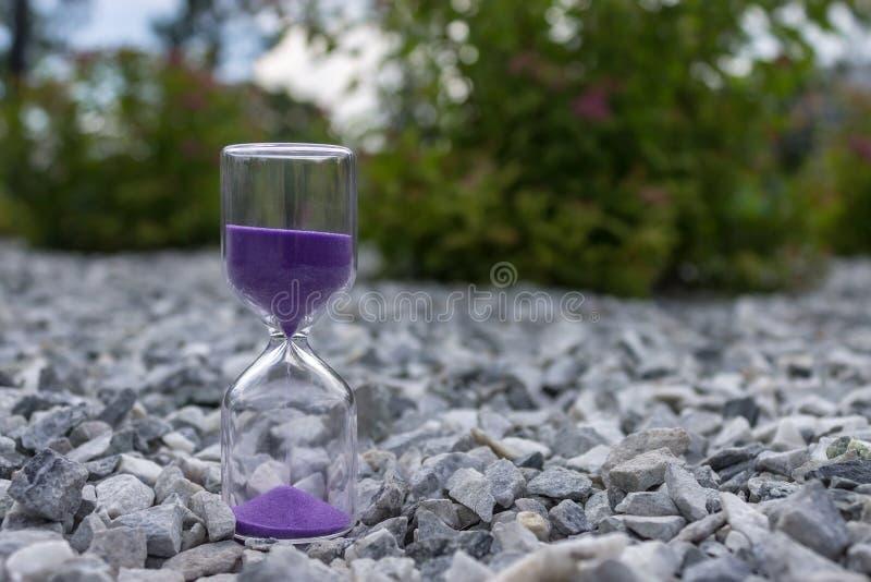 Hourglass na kamieniach w jawnym parku wśród krzaków fotografia royalty free