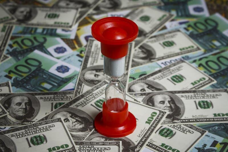 Hourglass na stosie dolary i euro zdjęcia stock