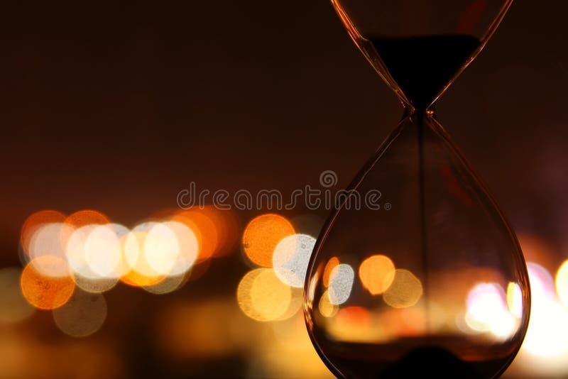 Hourglass nad bokeh miastem zaświeca jako czasu przelotny pojęcie dla biznesowego ostatecznego terminu obraz royalty free