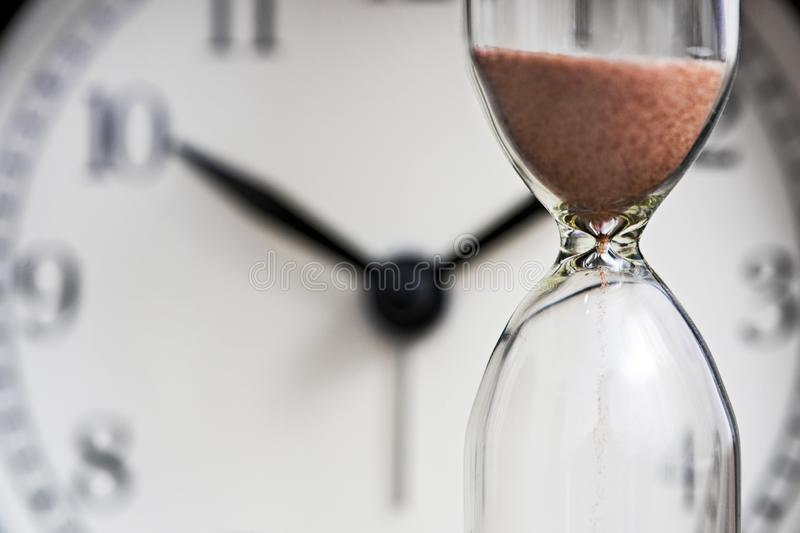 Hourglass and old alarm clock.  Sand clock on the background of the dial stock photography