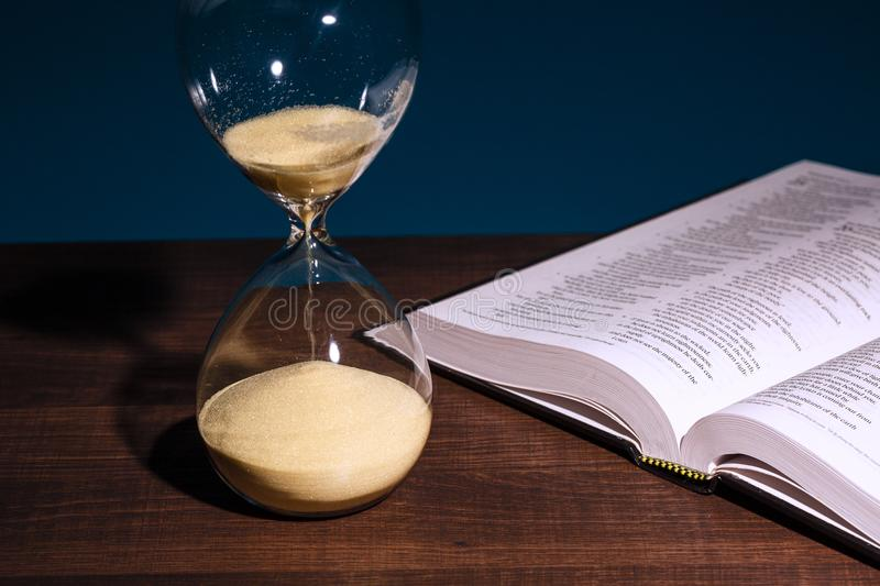 Hourglass and open Holy Bible stock photos