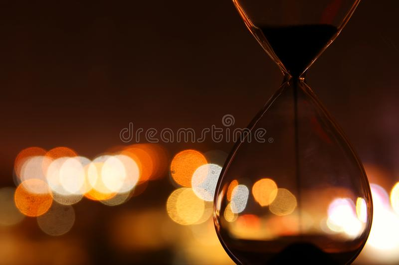 Hourglass over bokeh city lights as time passing concept for business deadline. royalty free stock image