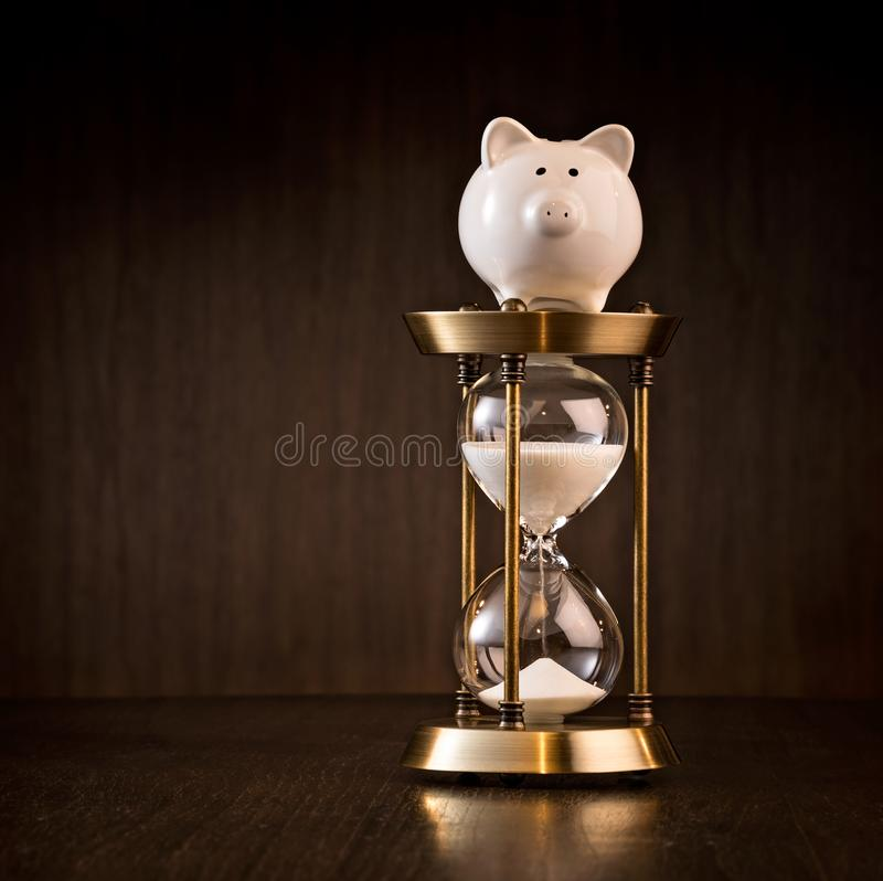 Hourglass and Piggy Bank concept stock photos