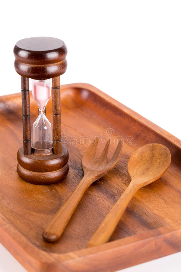 Hourglass on a plate with a fork and knife. For food and time conceptual themes royalty free stock images