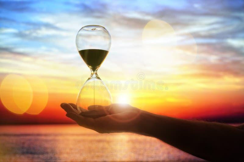 Hourglass przy zmierzchu pojęciem dla czasu omijania obrazy royalty free