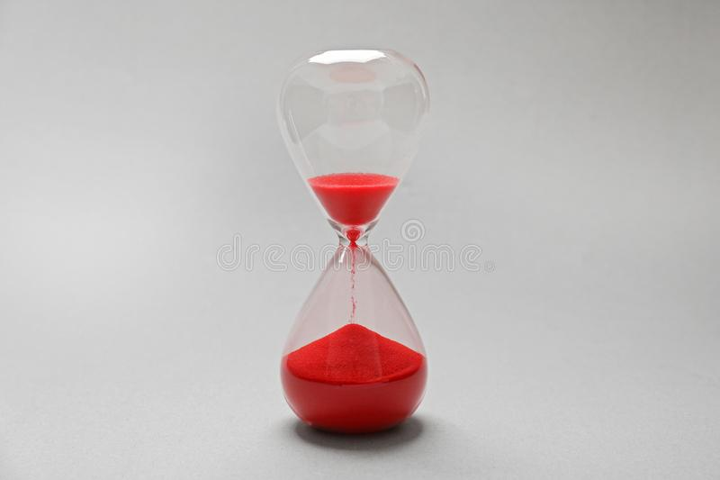 Hourglass with red sand. On light background stock photos