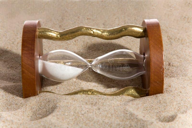 Hourglass on sand bacground. Hourglass on sea sand bacground royalty free stock photography