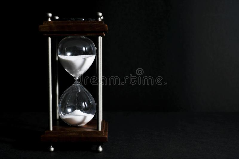 Hourglass, or sand clock isolated in black background, in low li. Hourglass, or sand clock is an old style time measurement, a symbol of the importance of stock photography