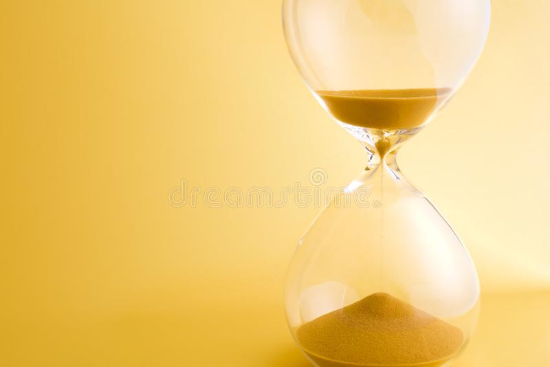 Hourglass with sand running through the bulbs on yellow background.  royalty free stock photos