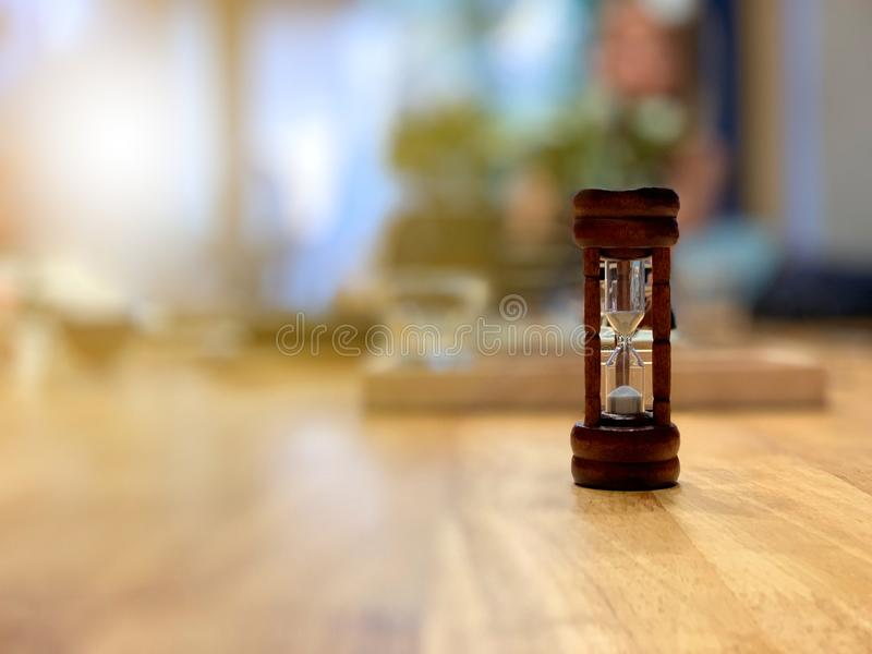 Hourglass with sand trickling on working table with morning sunshine. Hourglass with sand trickling on wooden working table with morning sunshine stock photography