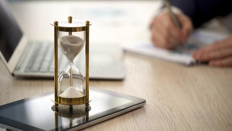 Hourglass standing on table with sand trickling, man working with graphs, data. Stock photo stock image