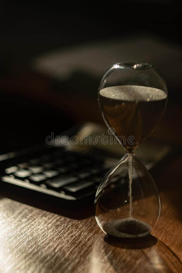 The hourglass is on the table. The flow of sand is irresistible, like time royalty free stock photo