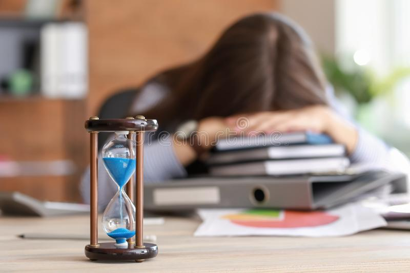 Hourglass on table of stressed businesswoman missing deadlines royalty free stock images