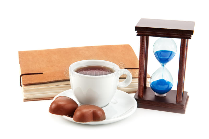Hourglass tea cup and a book. On a white background stock photos
