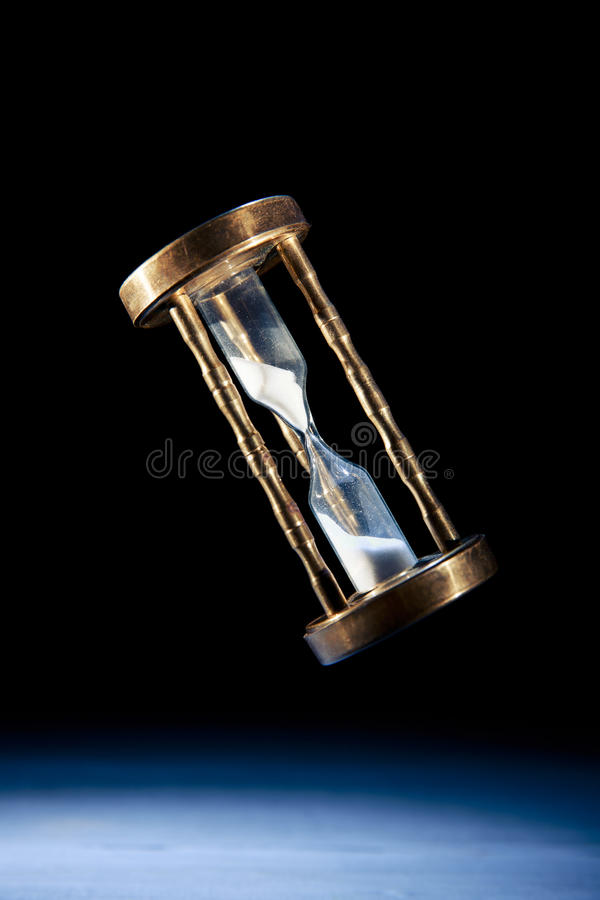 Hourglass, time concept with a high contrast image. Dramatic lit image of hourglass, time concept stock photography