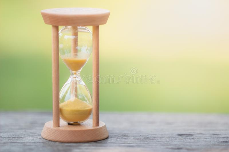Hourglass gold sand on orange background Evening atmosphere royalty free stock photos