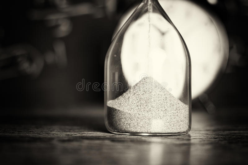 Hourglass on wood with a blackboard background. Hourglass against on wooden surface with a blackboard background stock photos