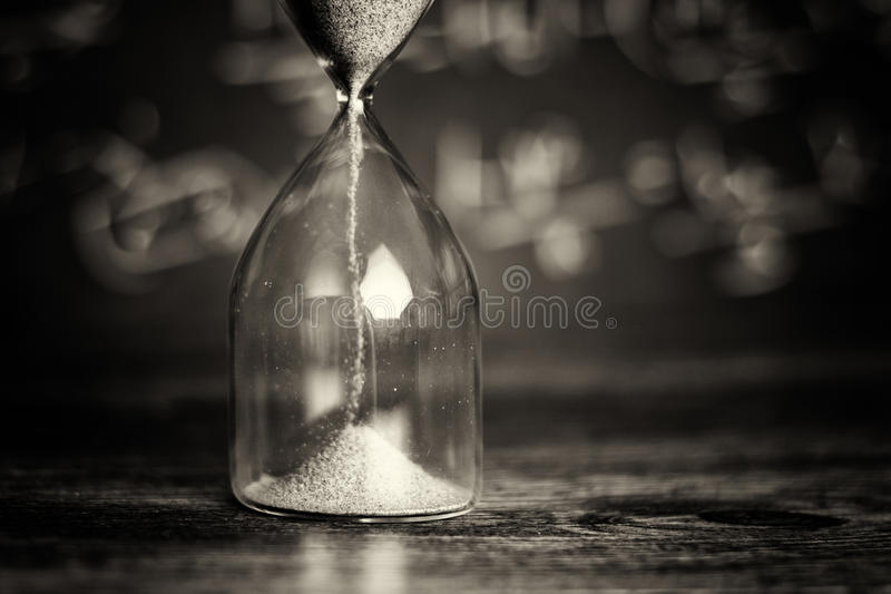 Hourglass on wood with a blackboard background. Hourglass against on wooden surface with a blackboard background royalty free stock photos