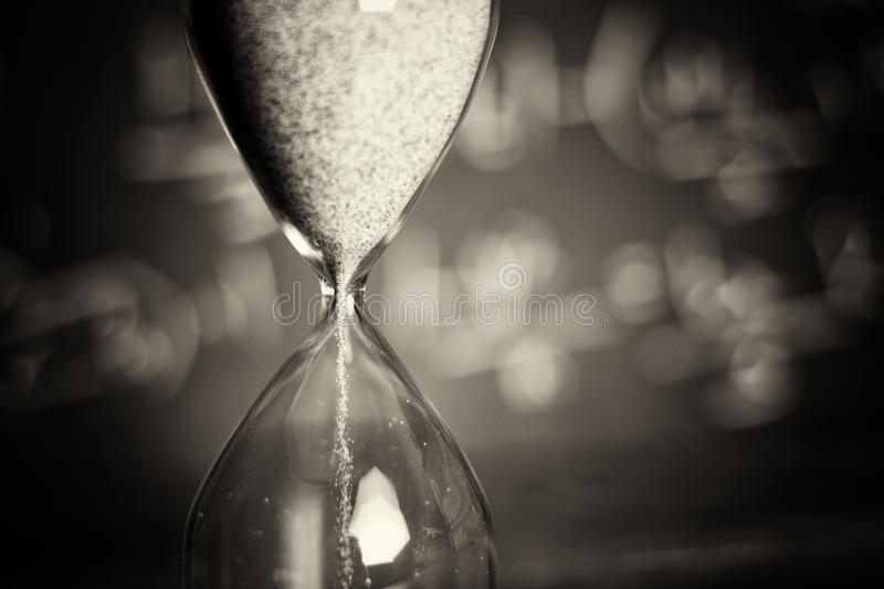 Hourglass on wood with a blackboard background. Hourglass against on wooden surface with a blackboard background stock image