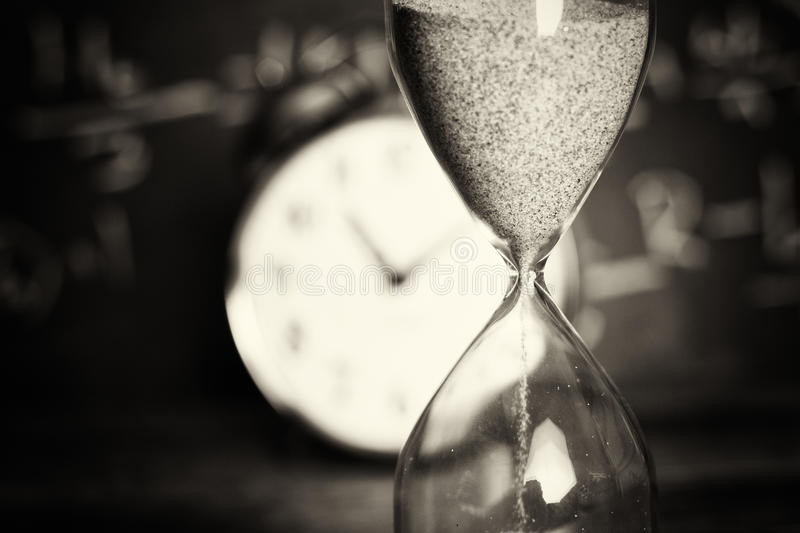 Hourglass on wood with a blackboard background. Hourglass against on wooden surface with a blackboard background stock photography