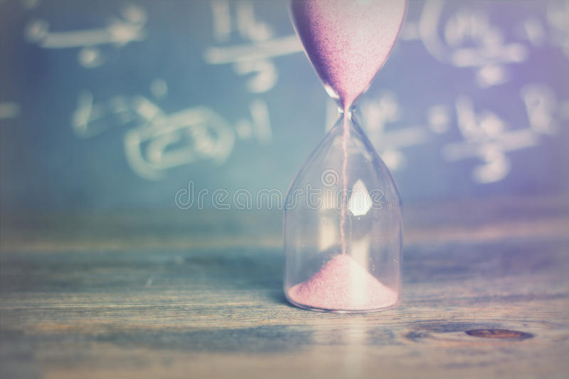 Hourglass on wood with a blackboard background. Hourglass against on wooden surface with a blackboard background royalty free stock image