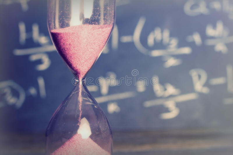 Hourglass on wood with a blackboard background. Hourglass against on wooden surface with a blackboard background royalty free stock photo